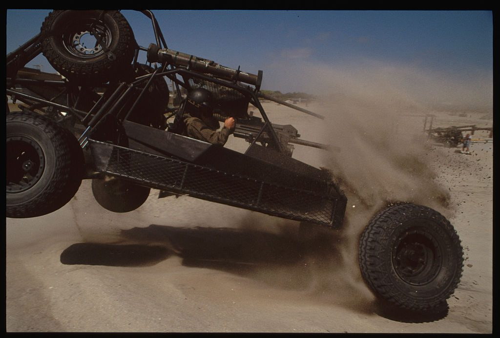 an extreme military grade off-road buggy tumbling through the desert sand