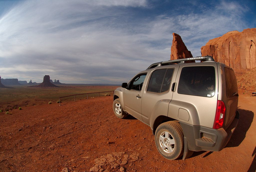 A grey Nissan Xterra off-roading in the desert.