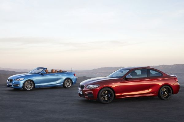 2018 BMW 230i Coupe and Convertible parked at a scenic outlook in the mountains.