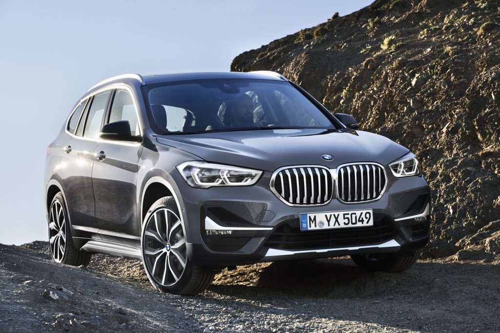 A charcoal grey 2020 BMW X1 driving down the countryside.