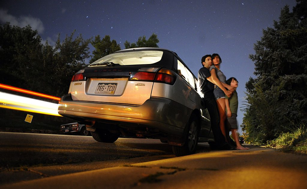A family stands outside of their Subaru Outback
