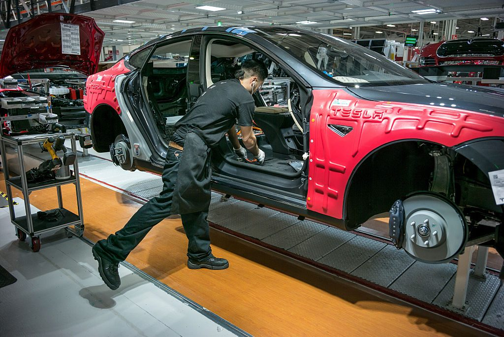 A Tesla worker assembles a car
