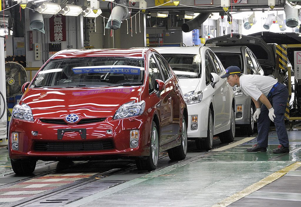 Workers assemble cars at a Toyota factory