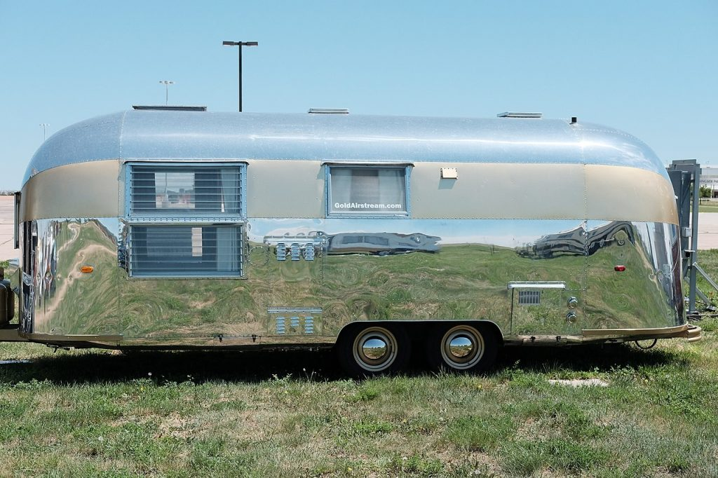 vintage Airstream RV and Camper model trailer parked on the grass at an event