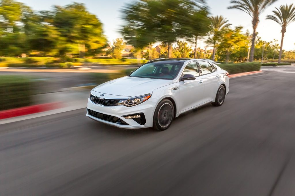 a white 2020 Kia Optima at speed on the road