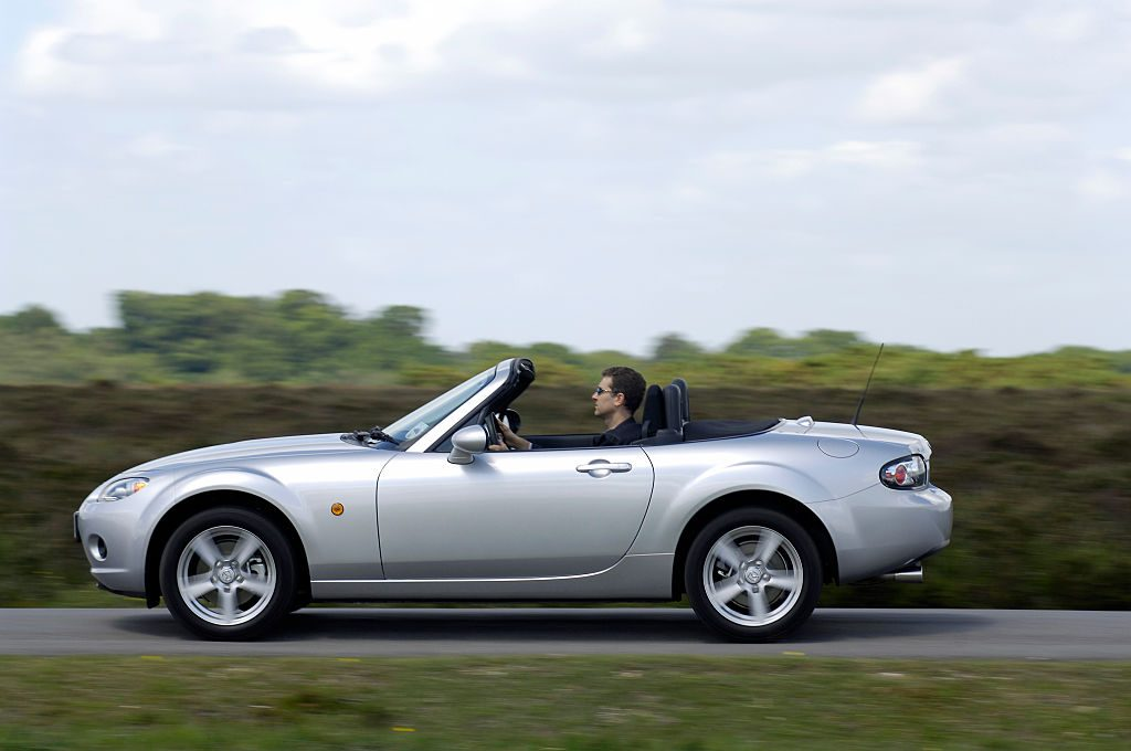 A Silver 2006 Mazda MX-5 on the road with the top down