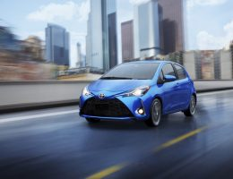a blue Toyota Yaris driving though a rainy city
