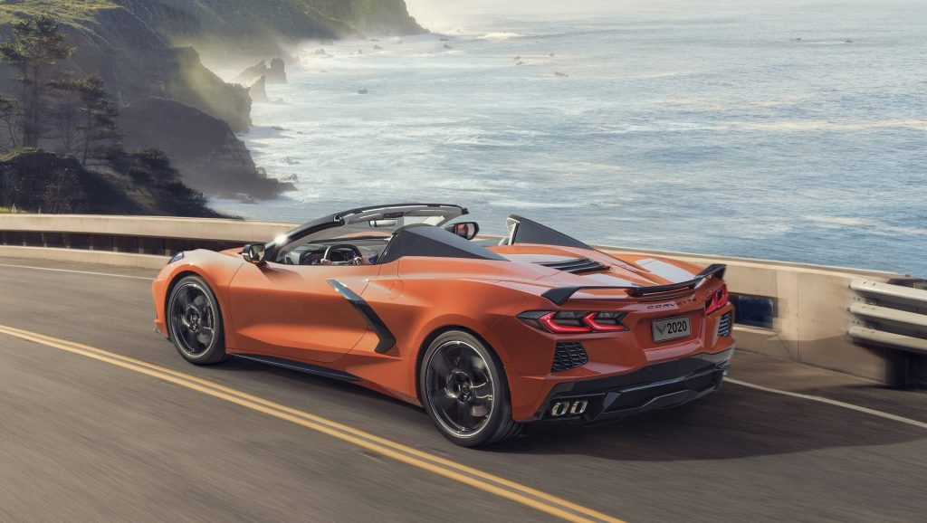 An orange Corvette is on a coastal road by cliffs