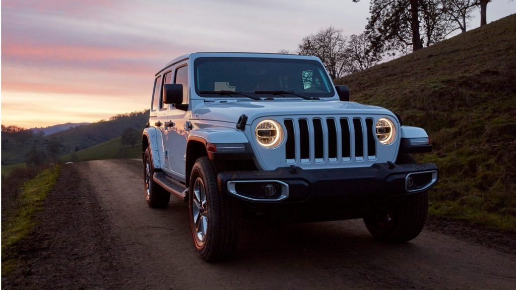 2020 Jeep Wrangler driving at night with its lights on
