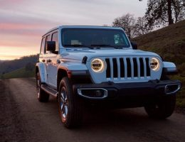popular Jeep Wrangler off-road SUV driving at night with its lights on