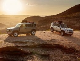 two land rover defenders in a remote desert scene with the sun giving backlighting