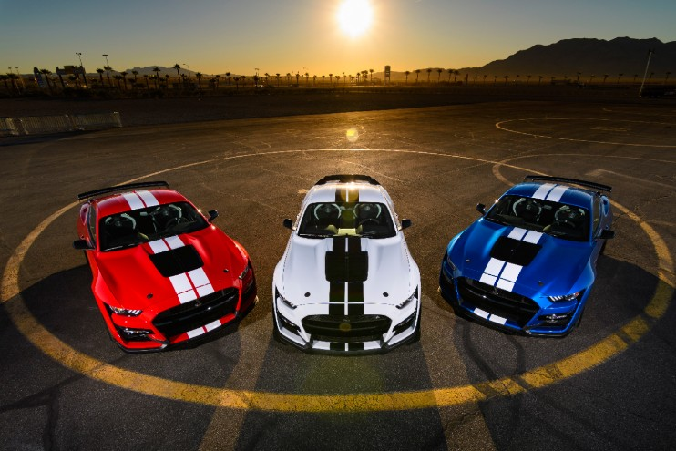 Three Ford Mustangs at sunset