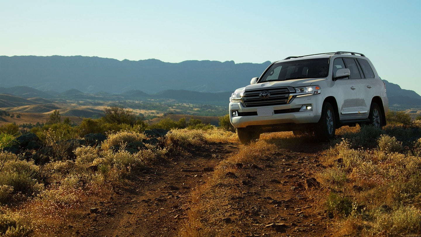 a white Toyota land cruiser driving off road on a mountain trail