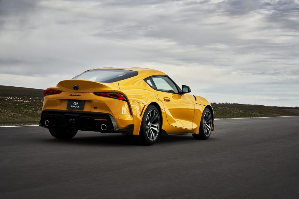 The rear view of a yellow 2021 Toyota Supra 2.0 on a racetrack