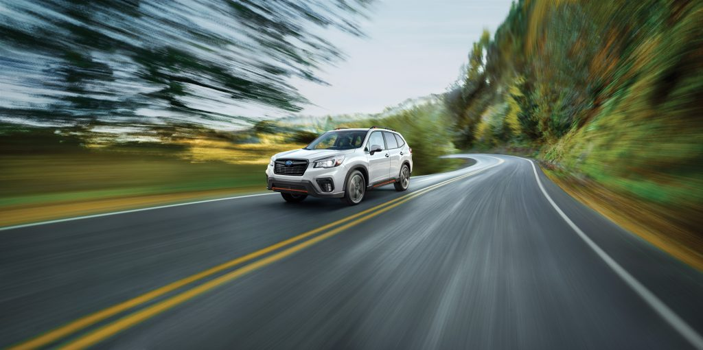a white subaru forester crossover SUV at speed on a scenic road