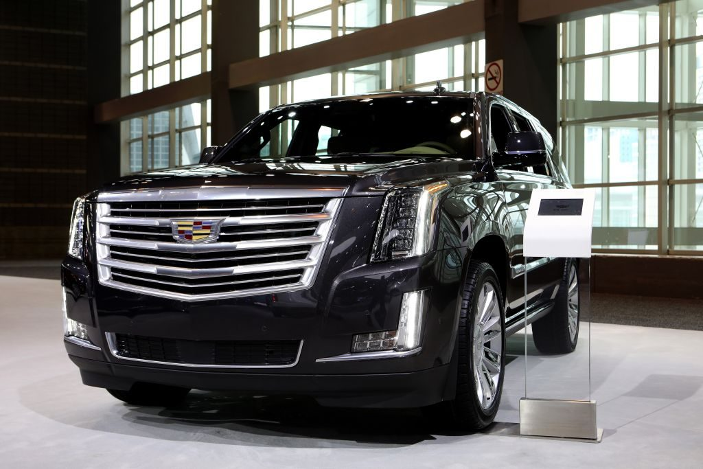A black Cadillac Escalade on display at an auto show