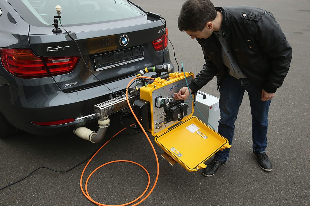 A man performs an emissions test on a car