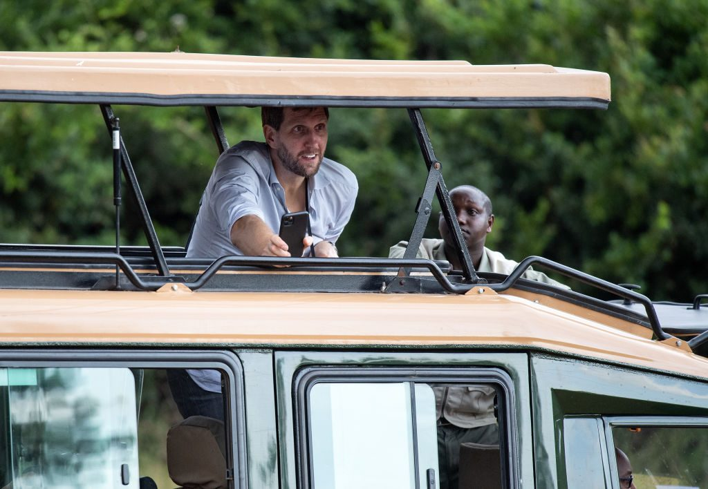 Dirk Nowitzki (l), a former basketball player, looks out from a jeep roof during a tour of Nairobi National Park by the delegation of the Federal President Steinmeier