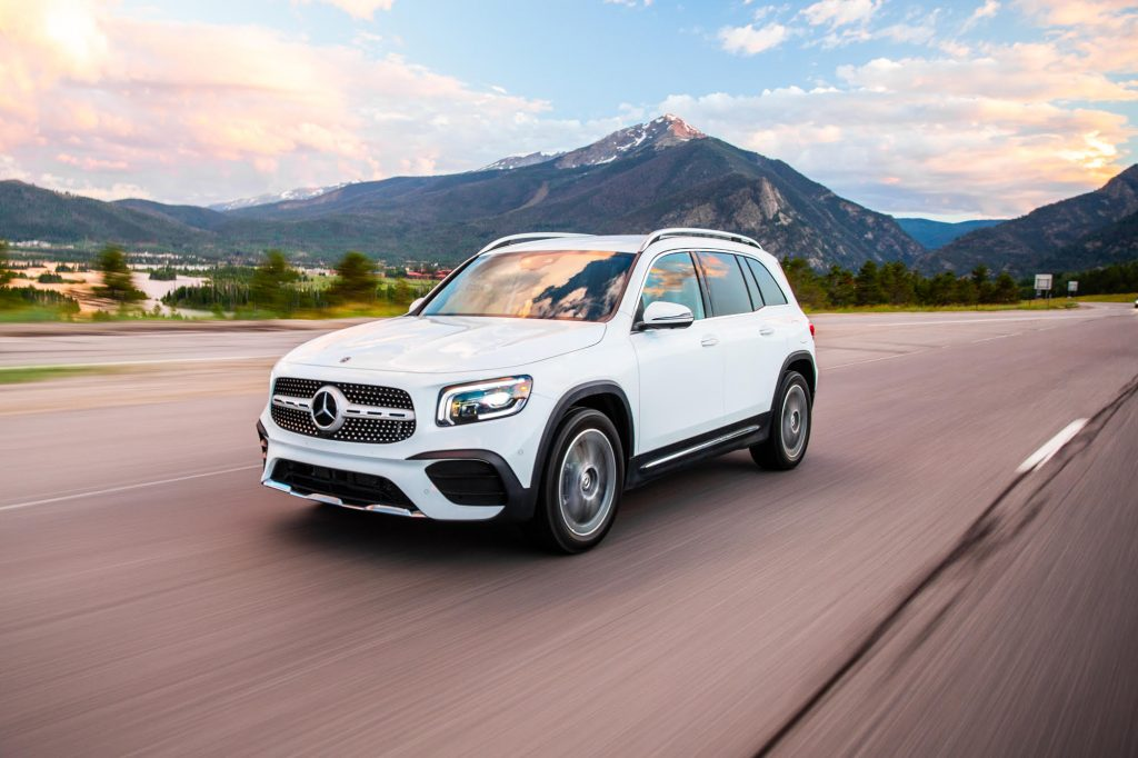 a white Mercedes-Benz GLB250 at speed on the an open country road.