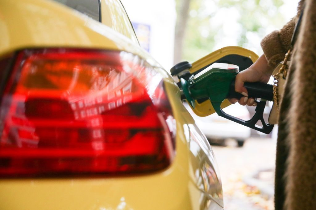 A motorist uses a pump as they re-fuel their car with unleaded petrol