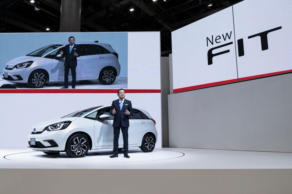 Honda Motor Co. President Takahiro Hachigo speaks in front of the company's redesigned Fit compact vehicle during a press conference at the Tokyo Motor Show