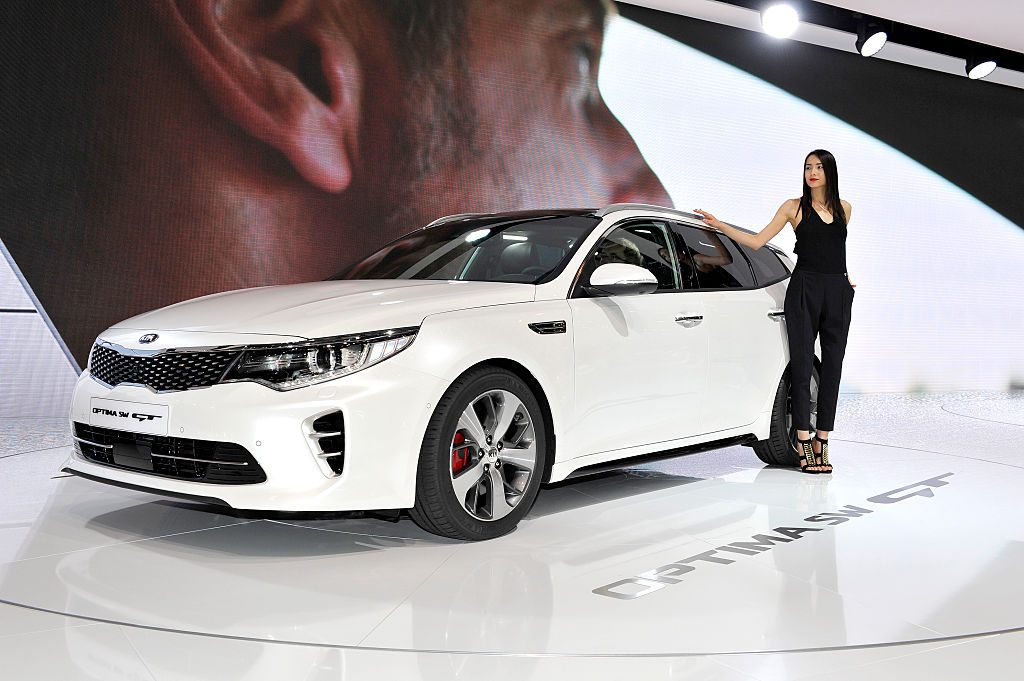 A model poses next to KIA Optima SW GT during the Geneva Motor Show 2016