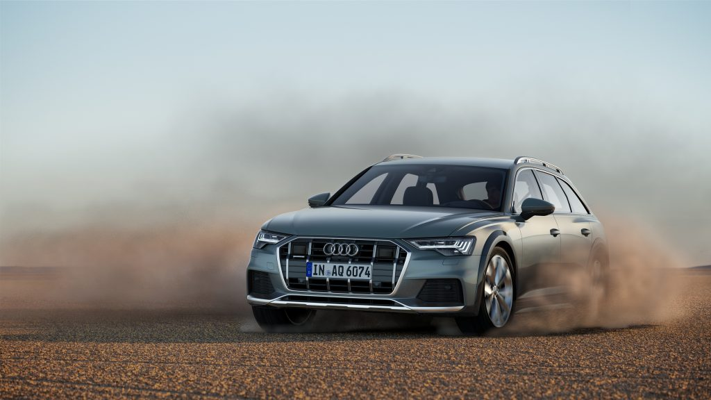 A silver Audi A6 station wagon plays in the desert.