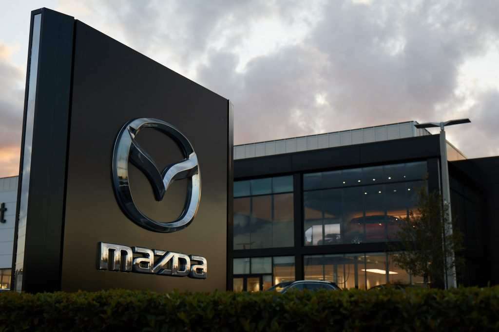 Mazda logo in front of a modern office building