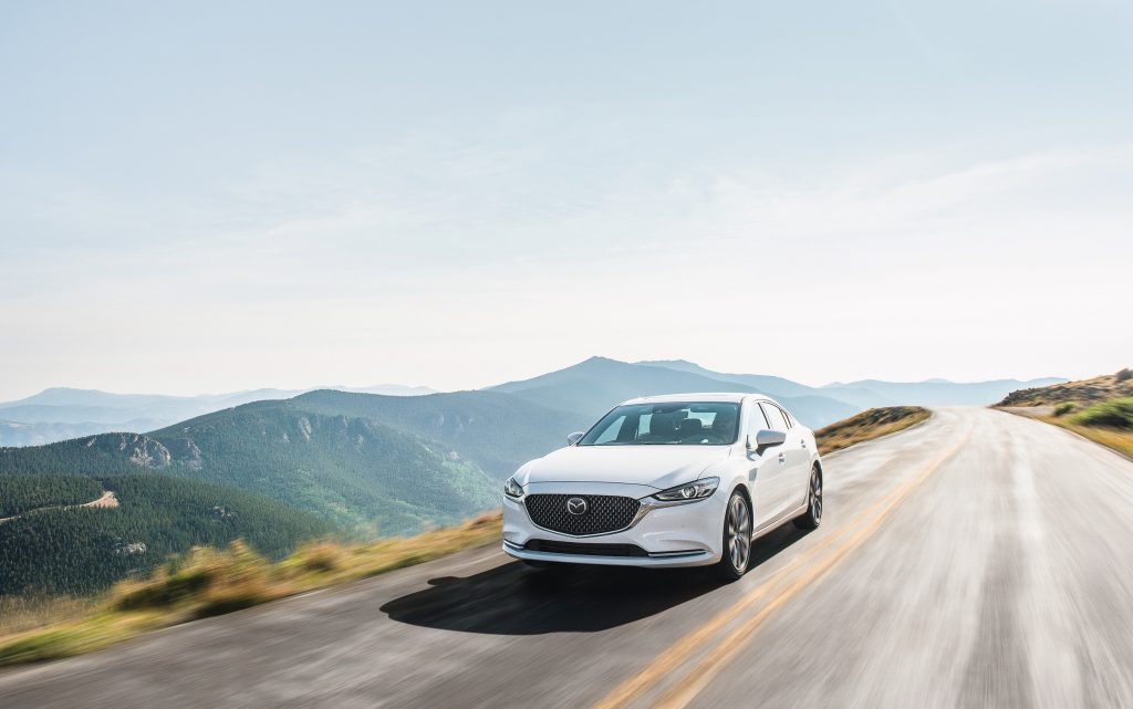 white mazda6 at speed on a scenic road against a mountainous backdrop