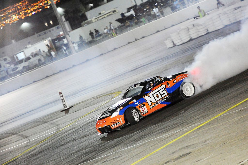 A blue and orange Nissan 350Z with a large white NOS decal drifts around a corner at the Las VEgas Motor Speedway