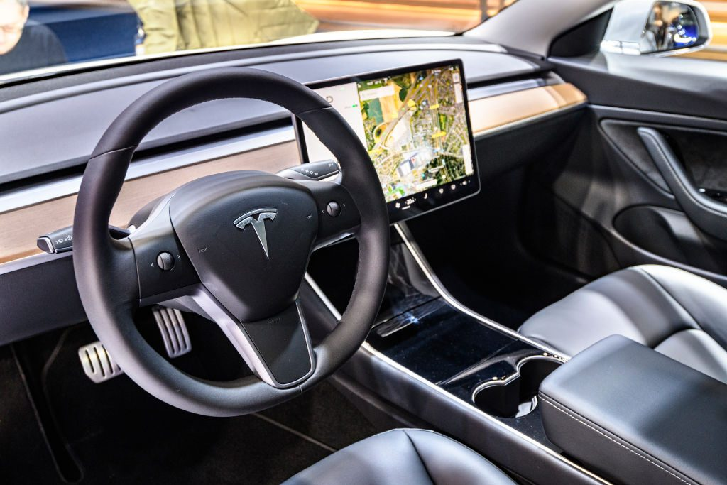 Tesla Model 3 compact full electric car interior with a large touch screen on the dashboard on display at Brussels Expo