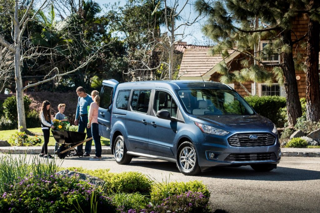 a blue Ford Transit Connect parked in a family driveway