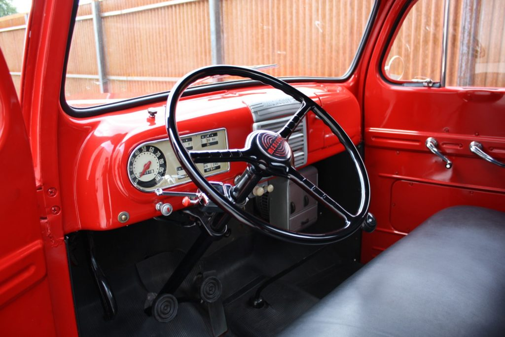 Red 1949 Mercury M47 pickup truck interior with black viny seat, red dashboard, and black 3-spoke steering wheel