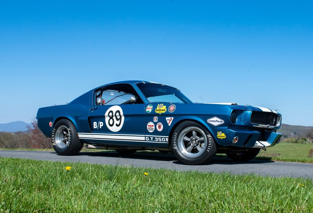 A 1965 Ford Shelby GT350 Mustang modified for racing, with blue paint, white racing stripes, and period-correct stickers
