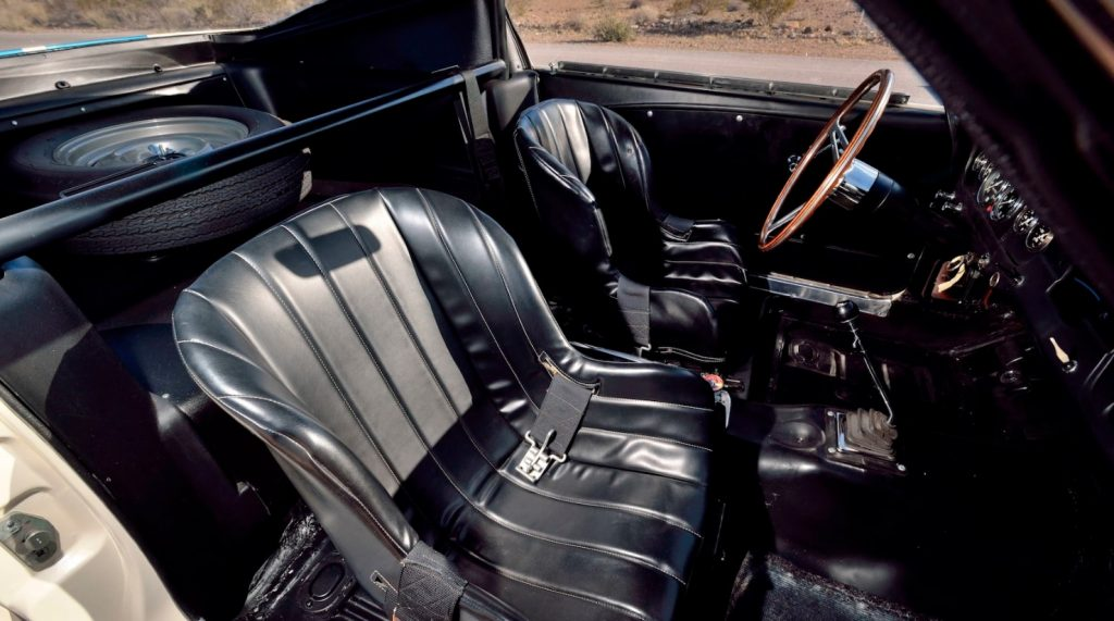 Black interior of 1965 Ford Shelby GT350R Mustang prototype, with fire extinguisher, bracing, and spare tire