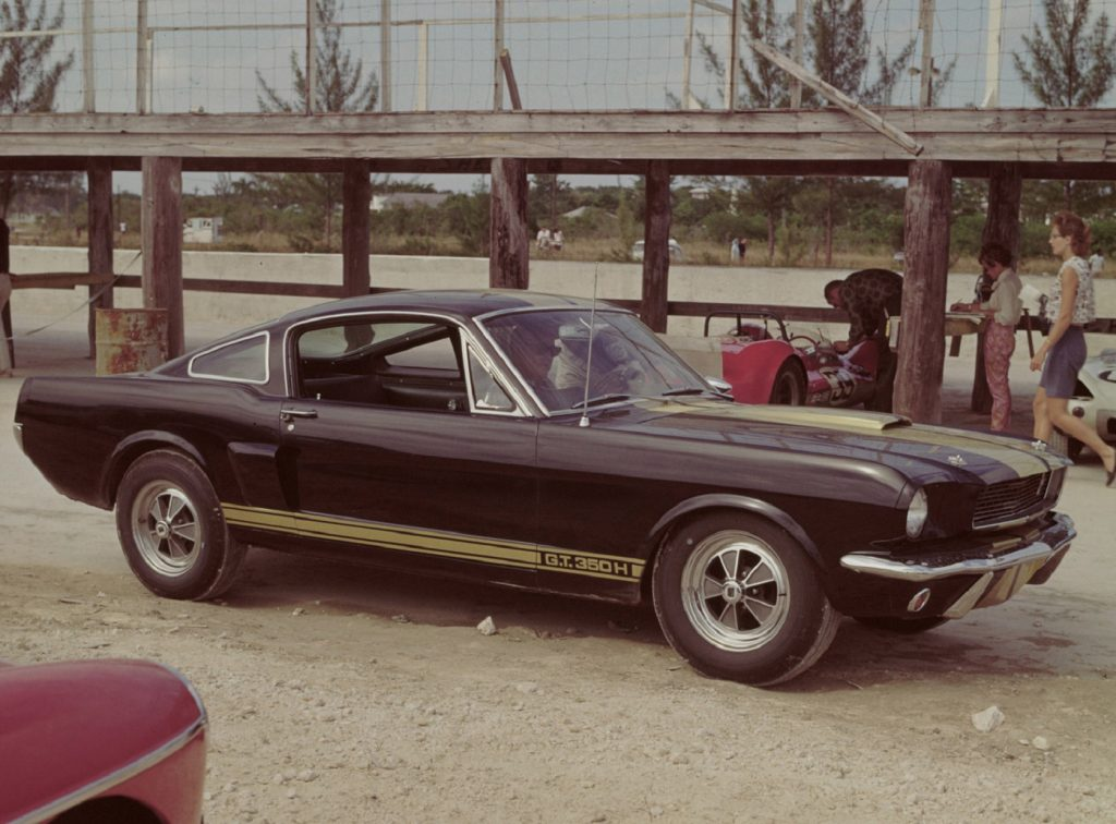 Black-with-gold-stripes 1966 Ford Shelby GT350H Mustang, parked with radio antenna extended