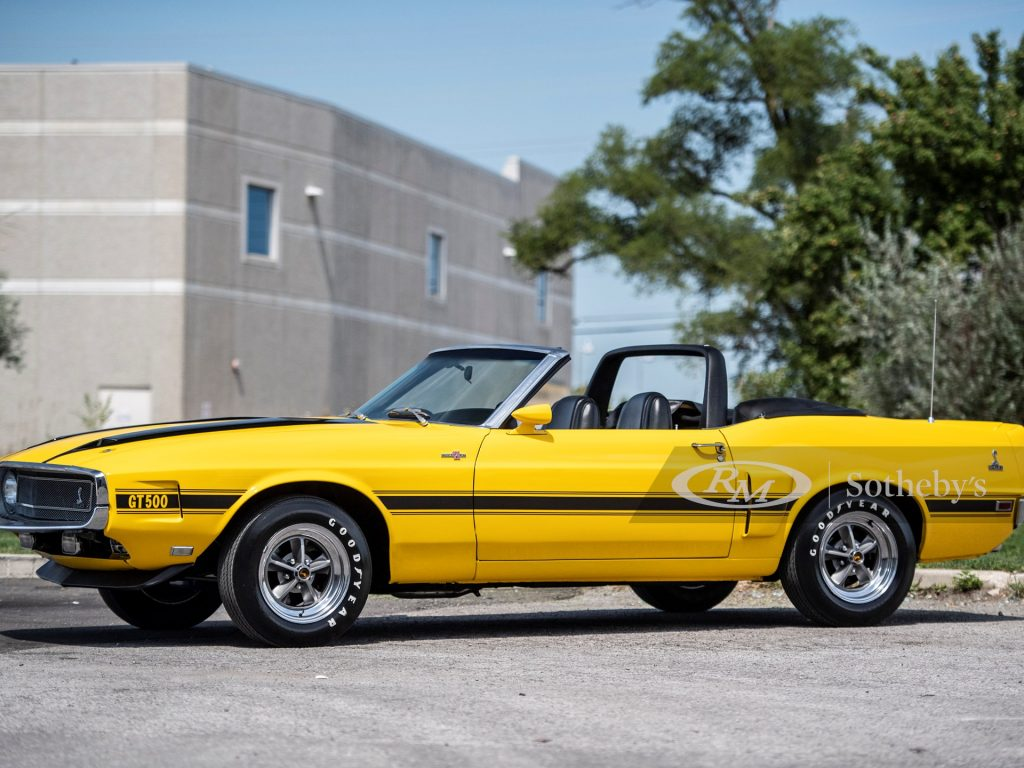A yellow Shelby GT500 sits in the sun with its top down