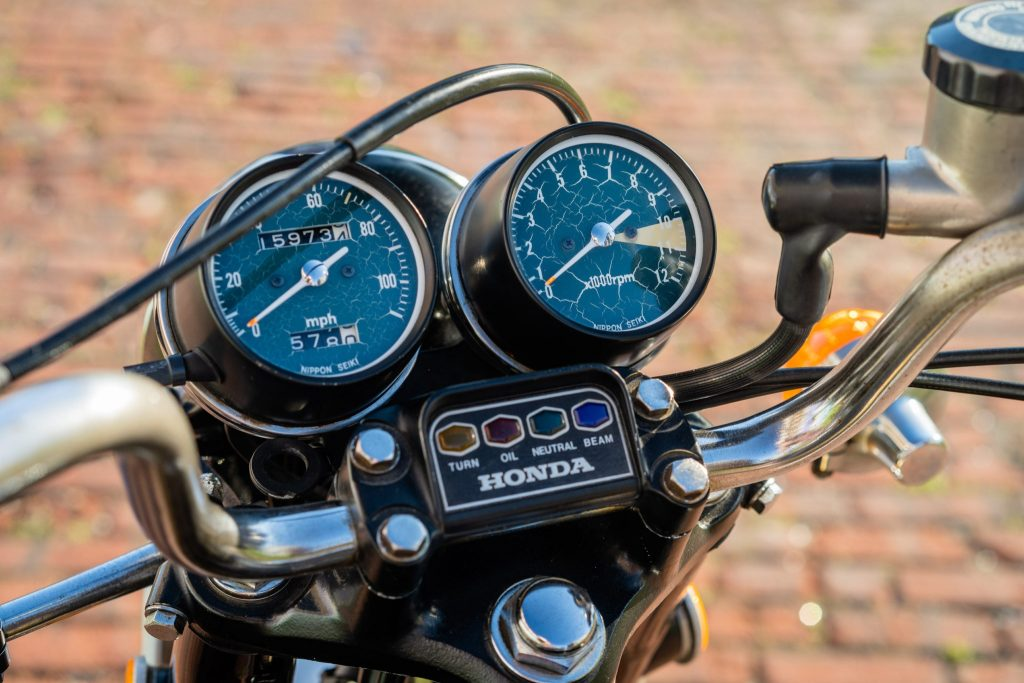 1973 Honda CB350 Four handlebar and gauges showing 10,000 RPM redline, speedometer, and indicator lights