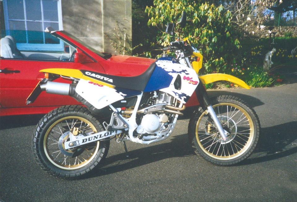 1995 Cagiva W16 600 with yellow, blue, and white livery, next to red car