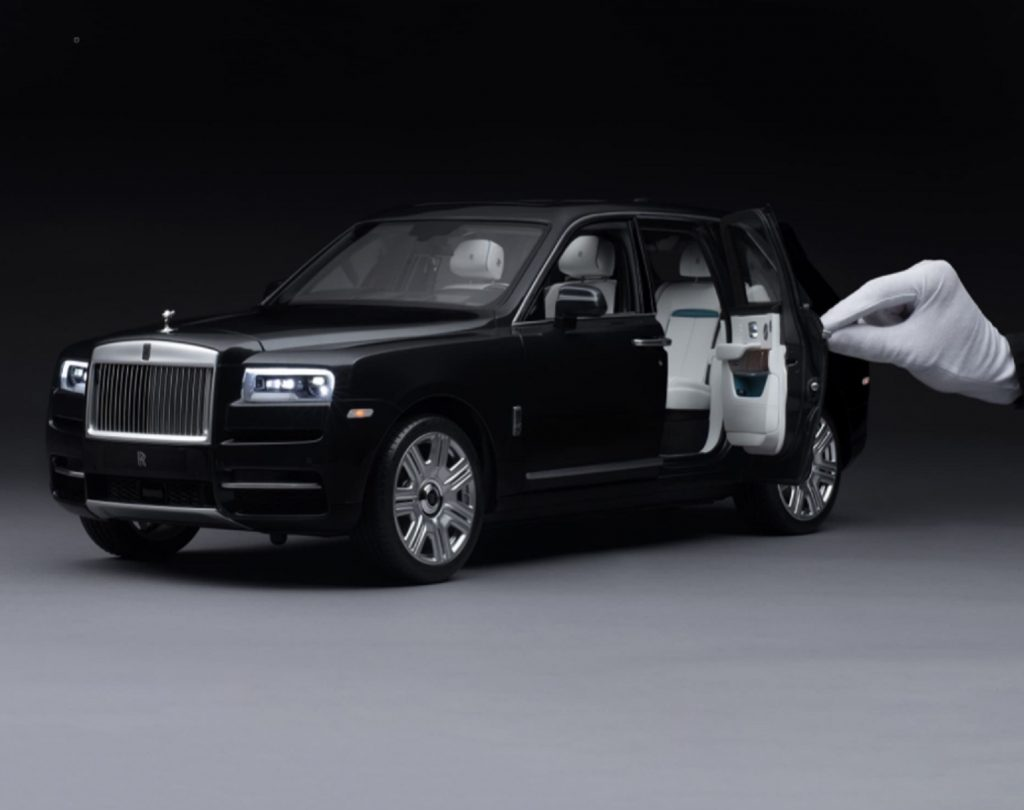 Black 1:8-scale Rolls-Royce Cullinan model with white-gloved hand for scale