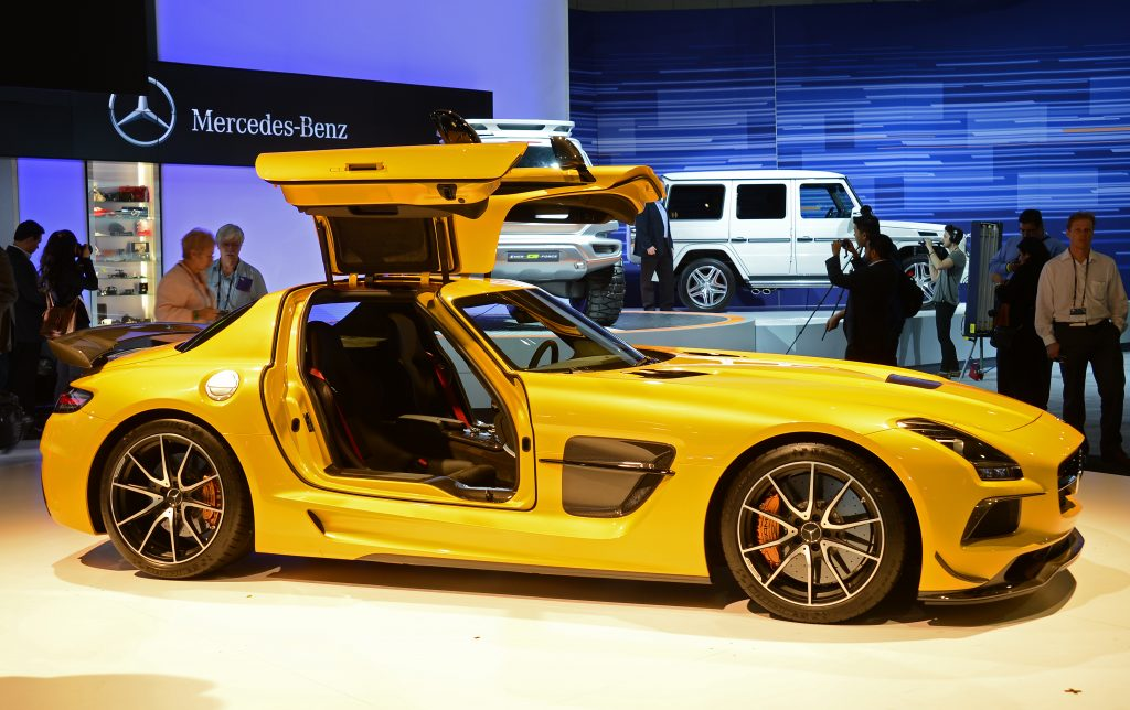 A yellow gullwing sports car from Mercedes sits on display at a car show