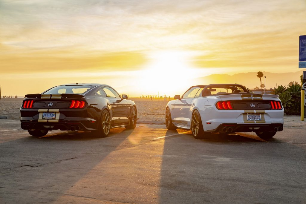 Black-with-gold-stripes 2019 Shelby GT-H Mustang and white-with-gold-stripes Mustang convertible face the sunset