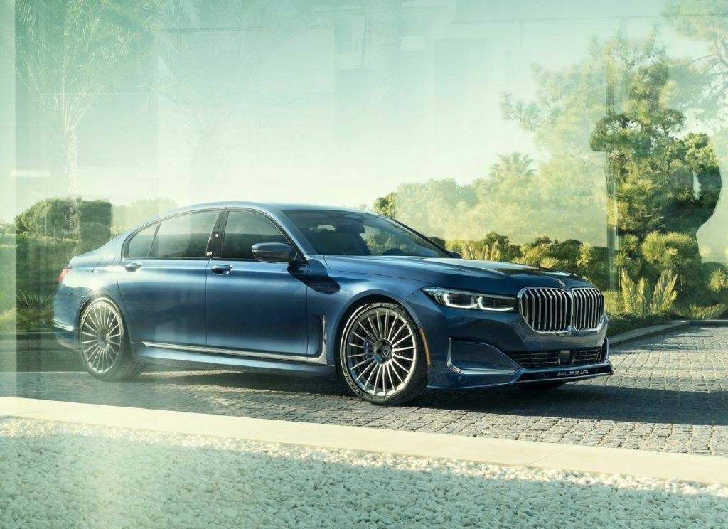 Dark blue 2020 Alpina B7 behind glass, with trees reflecting on the glass