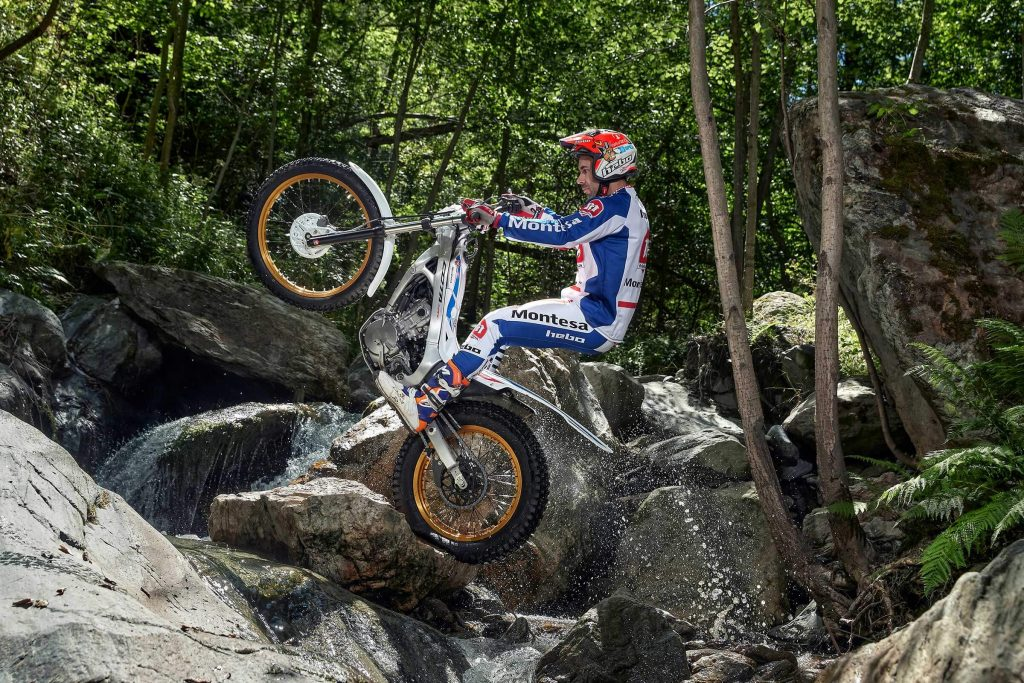 Silver 2020 Honda Montesa Cota 4RT260 jumping over large rocks and flowing stream