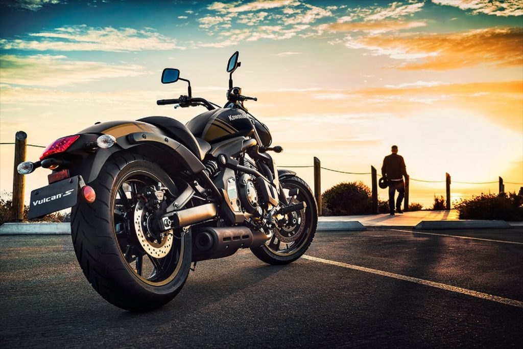 Side-rear view of a black-and-gold 2020 Kawasaki Vulcan S, parked in front of the setting sun