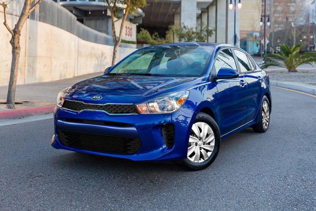 A blue 2020 Kia Rio scooting around the city.
