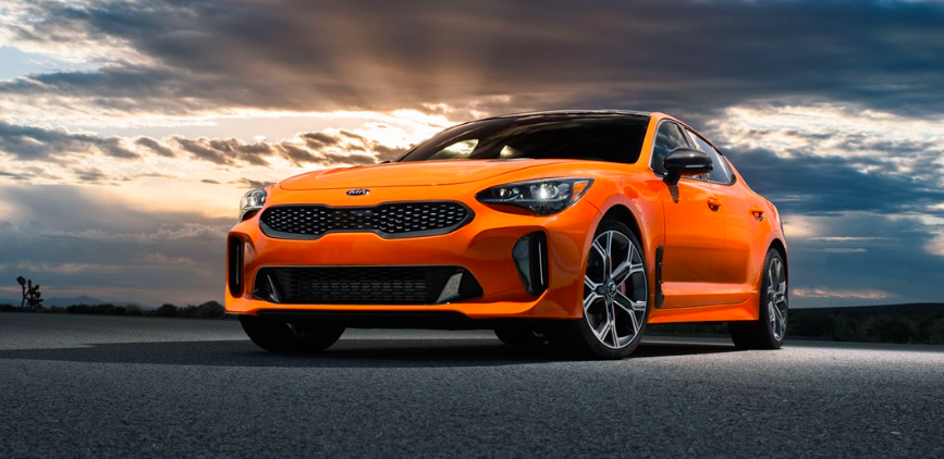 a bright orange Kia Stinger GTS parked outdoors on the road with a dreamy sky in the background