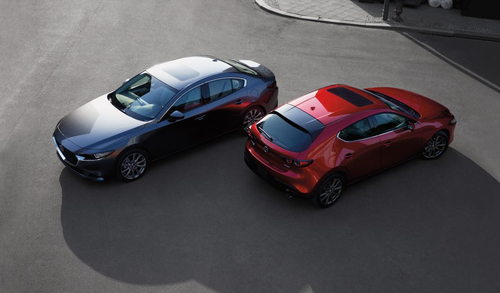 a gray sedan and a red hatchback from a sky view