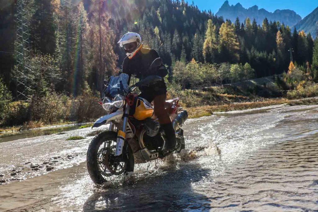 Yellow-trimmed 2020 Moto Guzzi V85TT Adventure being ridden through a mountain forest stream