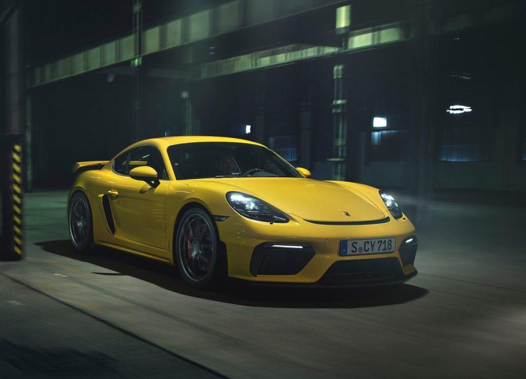 A yellow 2020 Porsche 718 Cayman GT4 drives through a city at night